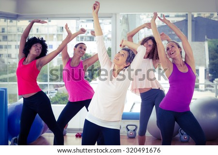 Happy women exercising with arms raised while looking up in fitness studio - stock photo