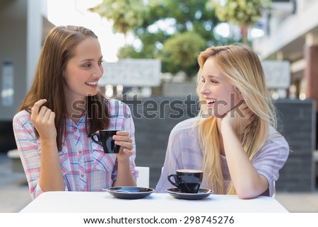 Happy women friends talking together outside at a cafe