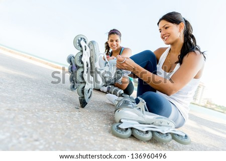 Happy women getting ready for skating outdoors - stock photo