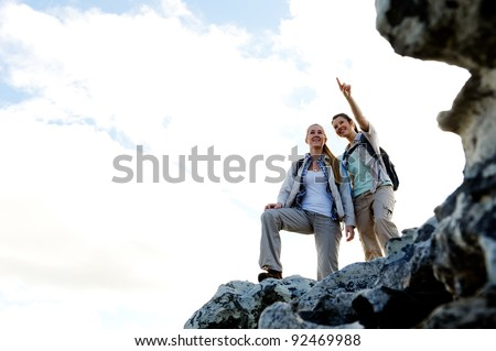 Happy women hikers stand on top of a rock and admire the view - stock photo