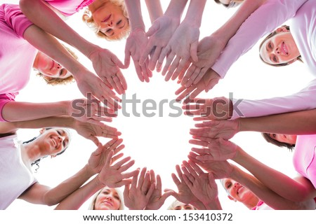 Happy women in circle wearing pink for breast cancer on white background