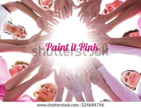 Happy women in circle wearing pink for breast cancer on white background - stock photo