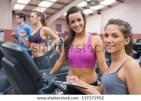 Happy women in the gym on treadmills carrying out assessment - stock photo