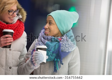Happy women looking at each other while holding disposable cups - stock photo