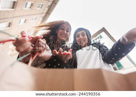Happy Women Looking into Shopping Bag. The point of view is inside the Bag and Women are Really Curious to See What's Inside - stock photo