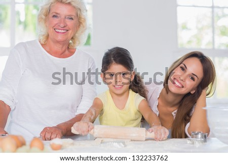 Happy women of a family baking together in the kitchen - stock photo