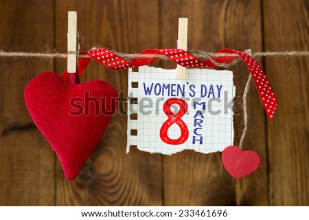 Happy Women's Day. Happy Women's Day on paper , hanging on a rope with red hearts. - stock photo