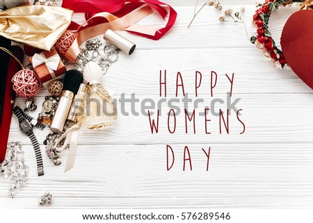 happy women's day text sign. fashion set flat lay with space for text. luxury essentials jewelry perfume presents on white rustic wooden table in soft morning light. modern woman stuff