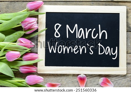 Happy Women's Day with tulips. Happy Women's Day on blackboard with pink tulips