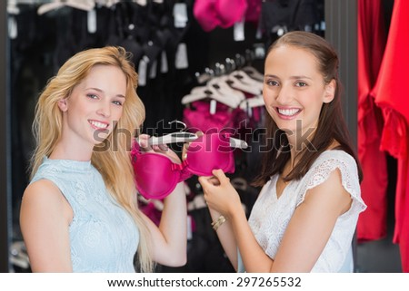 Happy women showing a bra in shopping mall - stock photo