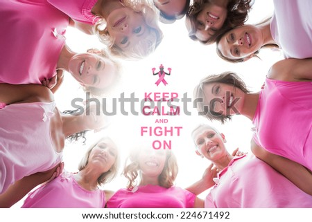 Happy women smiling in circle wearing pink for breast cancer against breast cancer awareness message - stock photo