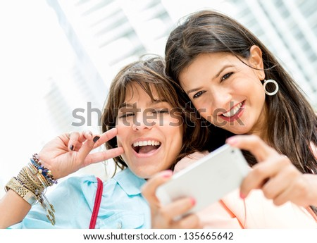 Happy women taking a self portrait with a mobile phone - stock photo