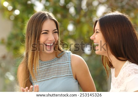 Happy women talking and laughing in a park with a green background - stock photo