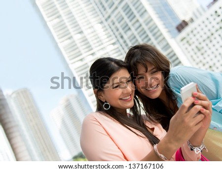 Happy women using an app on a smart phone - stock photo
