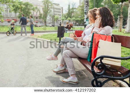 Happy women using mobile phone in the park after shopping
