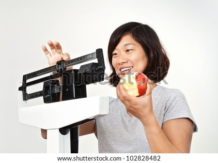 Happy women weighing herself on medical weight scale, smiling and pleased with her weight loss. - stock photo