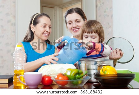 Happy women  with child together cooking veggie lunch with vegetables  in kitchen at home  - stock photo