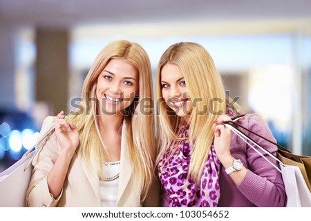 Happy women with shopping bags in shop - stock photo