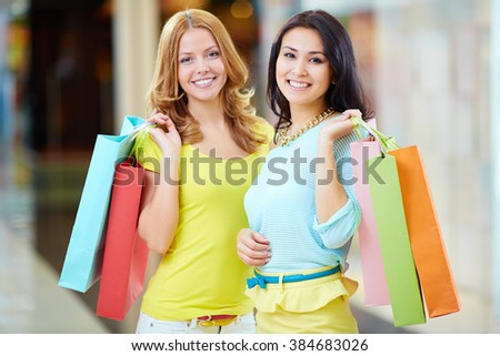 Happy women with shopping bags looking at camera - stock photo