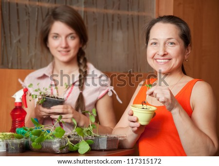 Happy women with various seedlings at home together