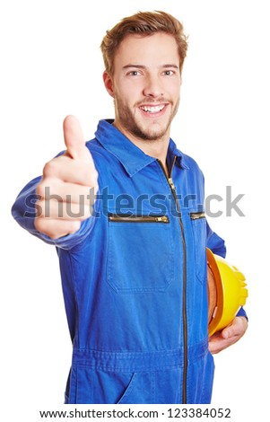 Happy worker in blue overall with hardhat holding his thumbs up - stock photo