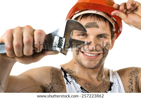 happy worker man, dirty in  safety helmet  with big wrench  in hands, turn on and smile, on white background, isolated - stock photo