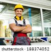 Happy worker wearing safety hat in a factory control room - stock photo