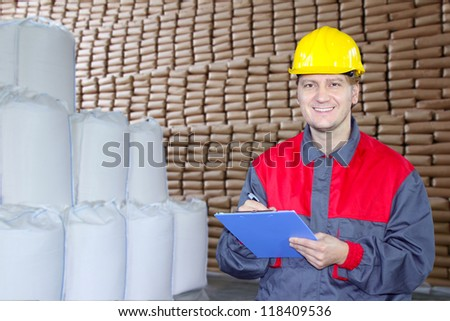 Happy worker writing on clipboard in warehouse - stock photo
