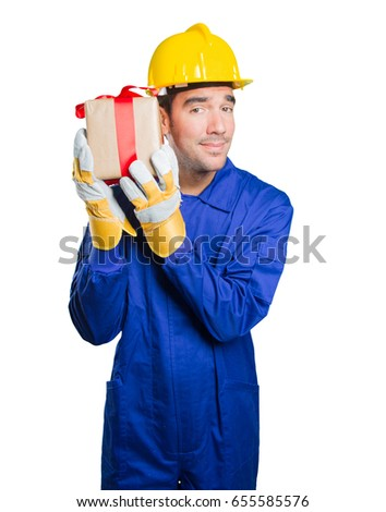 Happy workman holding a gift on white background