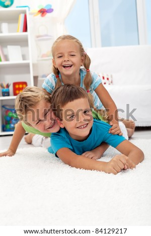 Happy wrestling kids laying in a pile indoors - stock photo