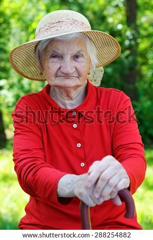 Happy wrinkled elderly woman relaxing in the garden - stock photo