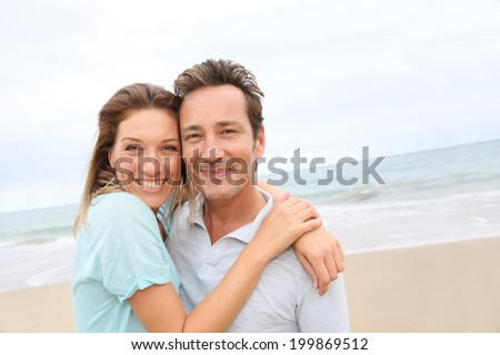 Happy 40-year-old couple enjoying day at the beach - stock photo