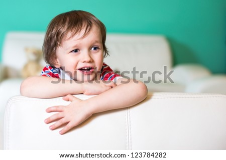 Happy 3 years baby boy sitting on leather white sofa in living room - stock photo