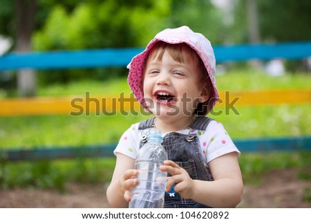 Happy  2 years baby with plastic bottle in park - stock photo