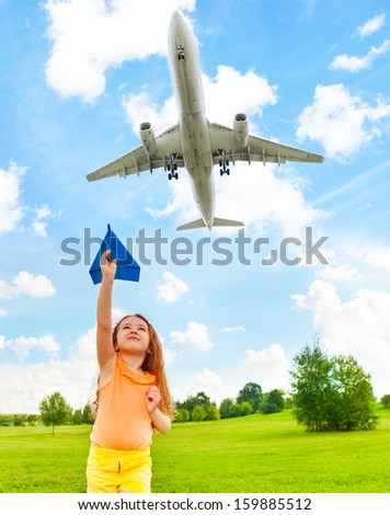 Happy 6 years old girl holding blue paper airplane with jet flying over in the sky - stock photo