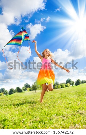 Happy 14 years old girl running in the field with big color kite