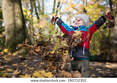 Happy 2.5 years old kid in a park playing with leaves - stock photo