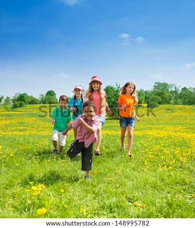 Happy 5-10 years old kids running together in the park - stock photo
