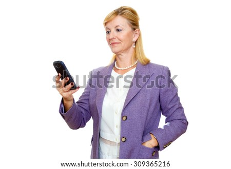 Happy 65 years old senior business woman in suit. Holding cell phone, smartphone in hand read and write sms. Isolated, plain white background - stock photo