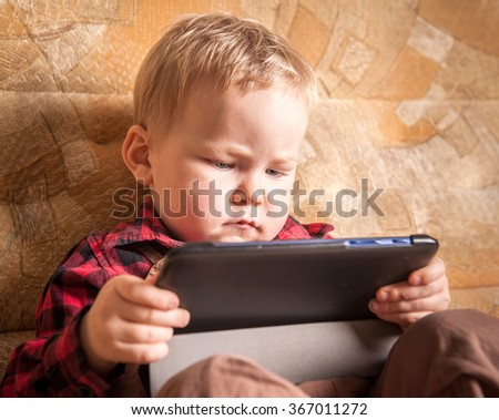 Happy 2 years old toddler  boy using tablet pc computer at home