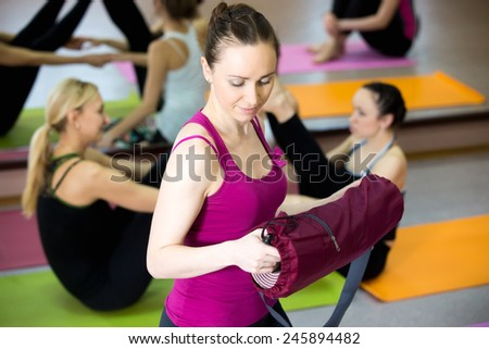 Happy yogi girl prepares for practice, unfolding, taking out pink yoga mat, her class partners do asana in pair on the background - stock photo