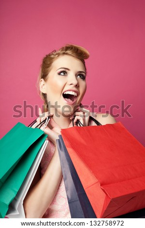 Happy yong woman with shopping bags isolated on pink - stock photo