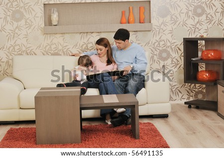 happy youg family relaxing in modern livingroom at home - stock photo