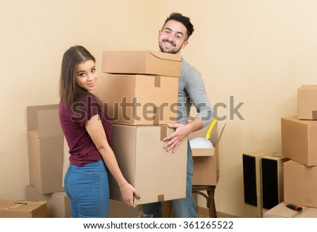 Happy young adult couple holding cardboard boxes - stock photo
