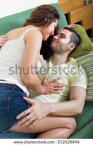 Happy young adult couple hugging and playing on sofa in living room  - stock photo