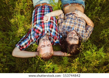 happy young adult couple lying on the grass - stock photo
