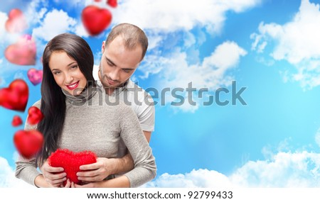 Happy young adult couple with red heart on romantic background with sky and clouds, embracing and laughing. Lots of copyspace - stock photo
