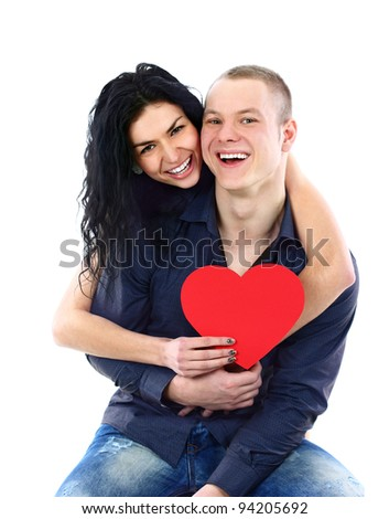 Happy young adult couple with red heart on white background, embracing and laughing - stock photo