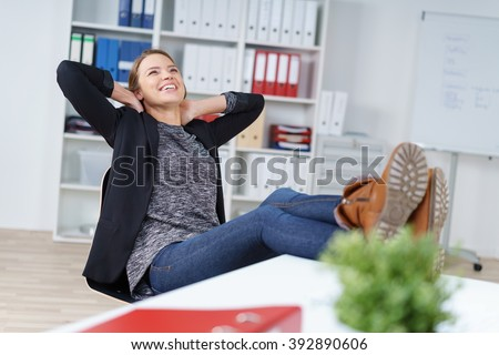 Happy young adult female in black blazer and blue jeans with hiking boots on white desk and arms behind her head