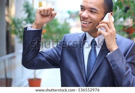happy young african american businessman on mobile phone - stock photo